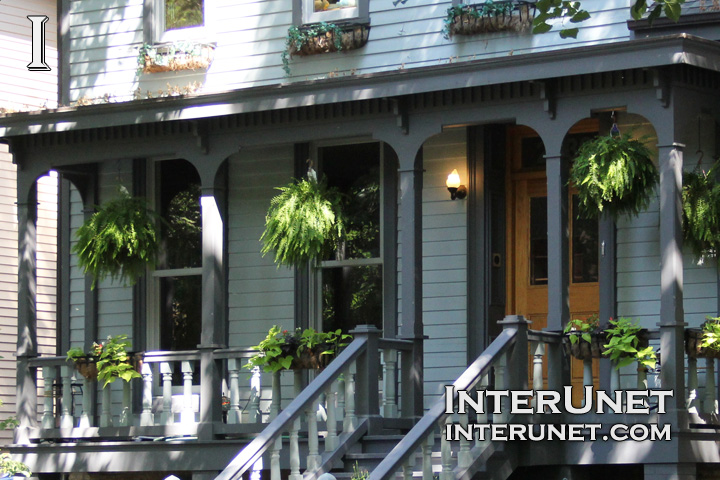 covered-wood-front-porch-decorated-with-green-plants