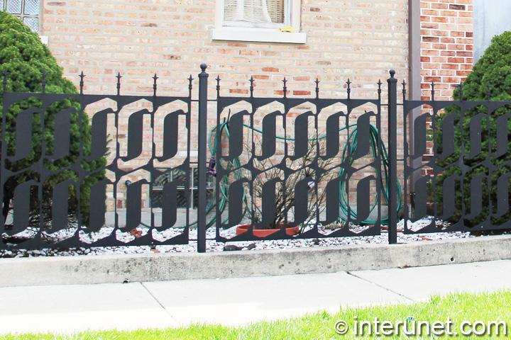 custom-designed-metal-fence-on-concrete-foundation