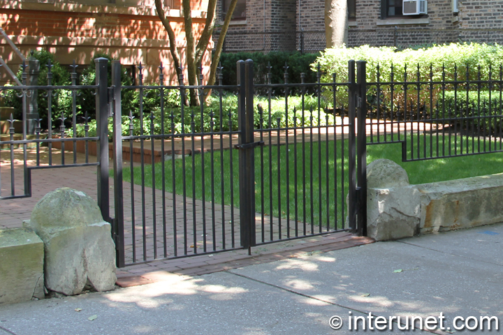 fence with steel gates painted black in combination with stones