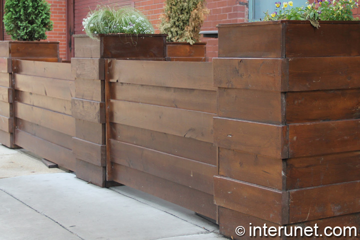horizontal fence with green plants on wood pillars