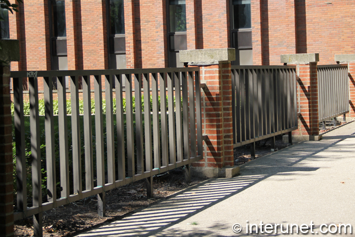 steel-fence-sections-mounted-on-brick-pillars