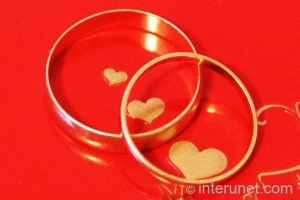 wedding-rings-on-red-background-with-hearts