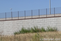 chain link fence on top of concrete blocks wall