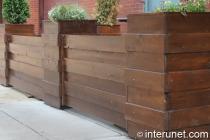 horizontal fence with green plants on wood pillars