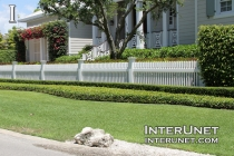 low-white-picket-fence-with-beautiful-landscaping