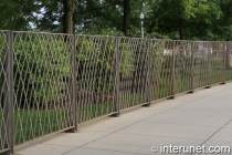 metal fence installed on top of concrete walkway